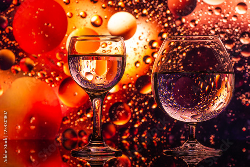 Leinwand Poster  transparent glasses with water with oily drops on colorful background
