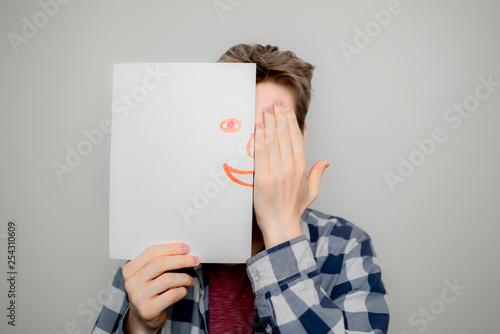 Fotografía  portrait of attactive man hold hand drawn emotion half face mask b