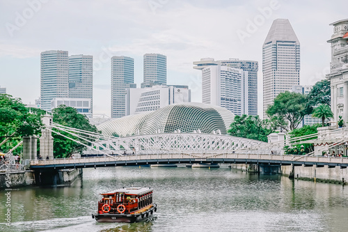 Photo Singapore - NOV 22, 2018: River tour boats with tourists are approaching historical suspension Cavenagh Bridge over the Singapore River in Singapore