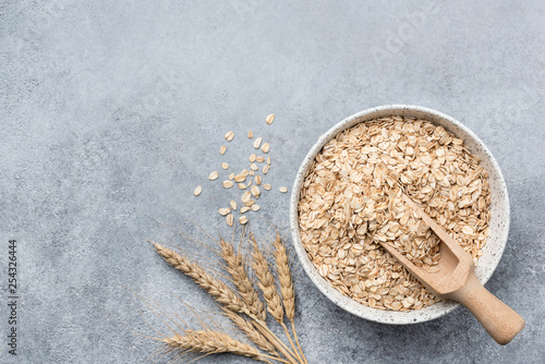 Photo Rolled oats, oat flakes in bowl on concrete background
