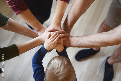 Fotografía  Stack of family people hands - father with children on light brown wooden texture laminate floor background indoors