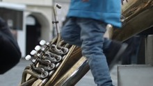 A Giant Brass Instrument Lies Against Stair On The Street As A Child Steps Past In Melnik, Czech Republic.