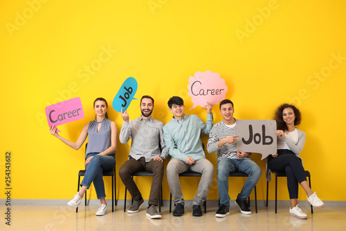 Young people holding speech bubbles with words JOB and CAREER indoors Wallpaper Mural