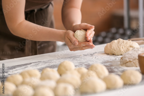 Fototapeta  Female baker cooking buns in kitchen