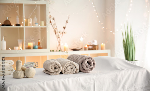 Fototapety, obrazy: Soft towels with herbal bags on table in spa salon
