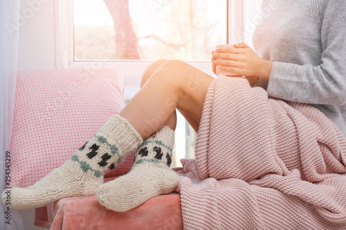 Photo sur Toile The Young woman drinking hot tea near window at home