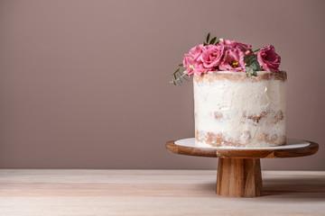 Slatka torta s cvjetnim dekorom na stolu u pozadini boja