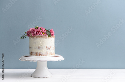 Foto Sweet cake with floral decor on table against color background