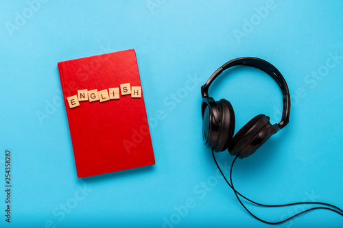 Valokuvatapetti Book with a red cover with text English and black headphones on a blue background