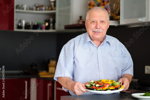 Fotografie, Obraz  Smiling Senior man 70-75 yers old, holding plate with fresh vegetables on her kitchen at home