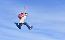 青空でジャンプする小学生の女の子(ランドセル)