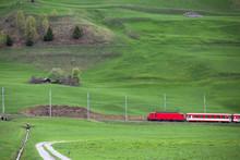 Regionalzug In Der Grünen Landschaft Im Kanton Graubünden. Zug Fährt Durch Die Schweiz.