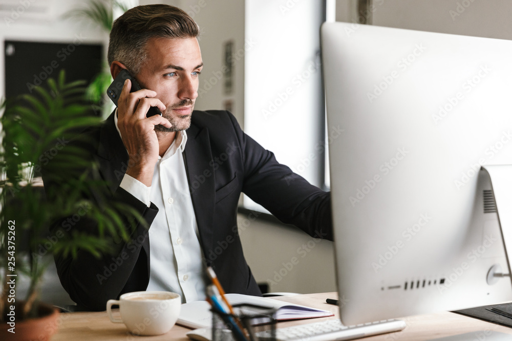 Fototapeta Image of smart businessman talking on cell phone while working on computer in office