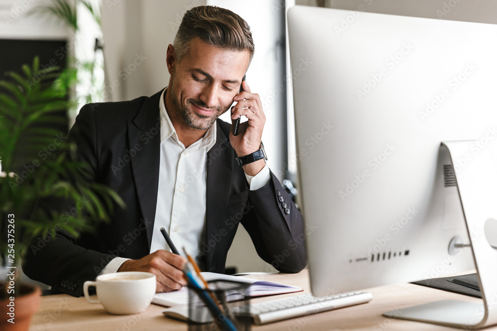 Fototapeta Image of handsome businessman talking on cell phone while working on computer in office