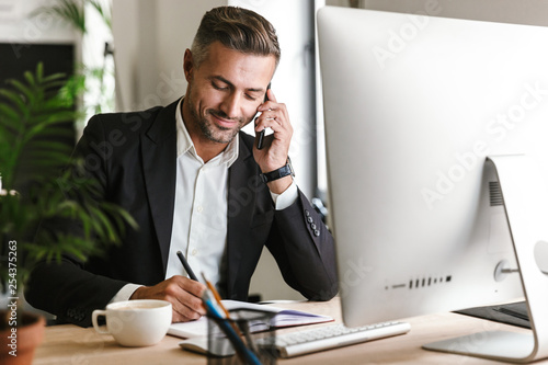 Fototapeta Image of handsome businessman talking on cell phone while working on computer in office obraz