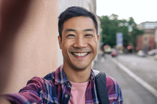 Smiling Young Asian Man Taking Selfies On A City Street