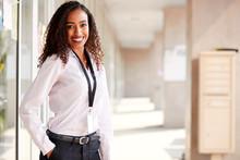 Portrait Of Smiling Female School Teacher Standing In Corridor Of College Building