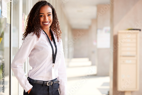 Photographie Portrait Of Smiling Female School Teacher Standing In Corridor Of College Buildi