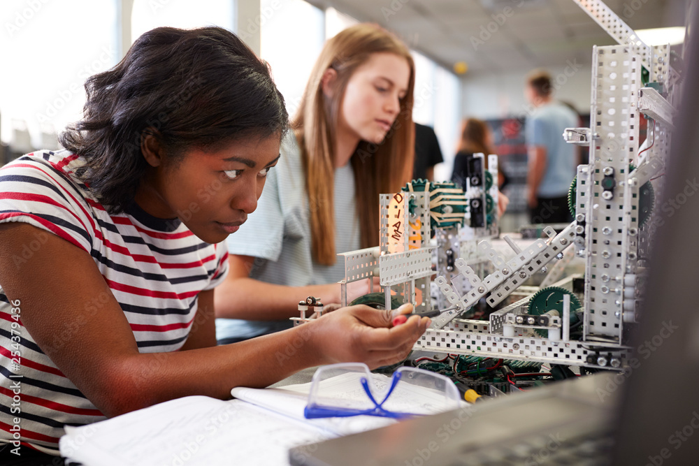 Fototapety, obrazy: Two Female College Students Building Machine In Science Robotics Or Engineering Class