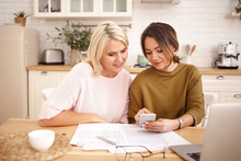 Indoor Image Of Beautiful Dark Haired Young Woman Holding Mobile Phone, Showing Her Attractive Middle Aged Mother How To Pay Mortgage Or Apartment Rent Online Using Application On Electronic Gadget