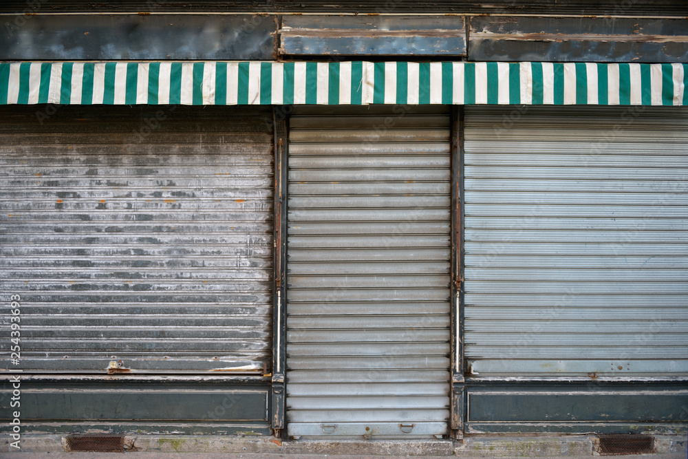 Fototapeta Old store. Ancient storefront with metallic closed curtains. Abandoned shop business.