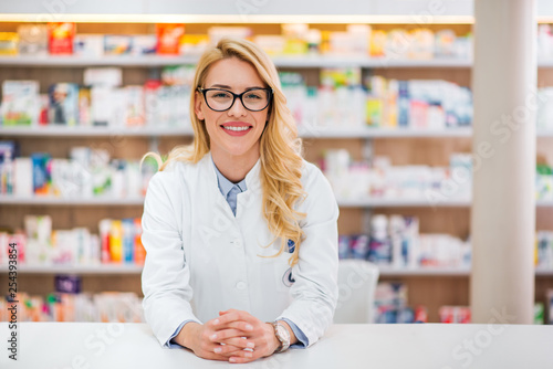 Carta da parati  Portrait of a beautiful blonde pharmacist leaning on counter at pharmaceutical store