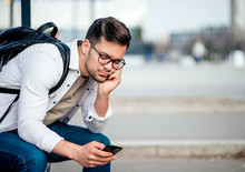 Casual Bored Young Man With Backcpack Sitting On Bench And Waiting For Bus, Using Smartphone.