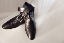 Men's Black Leather Shoes On A White Shelf With A Belt. Men's Accessories
