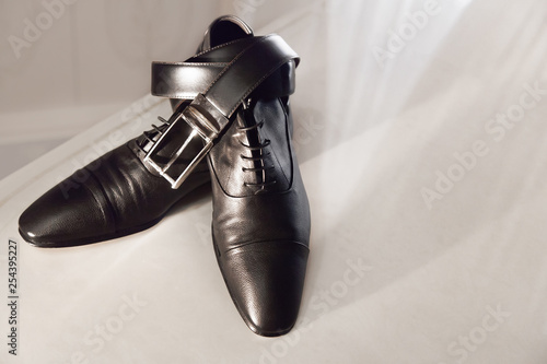 Vászonkép  men's black leather shoes on a white shelf with a belt