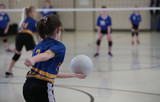 young girls serves a volleyball