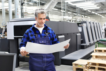 Drukarnia offsetowa. Drukarz z arkuszem wydruku stoi przed maszyna drukarską.