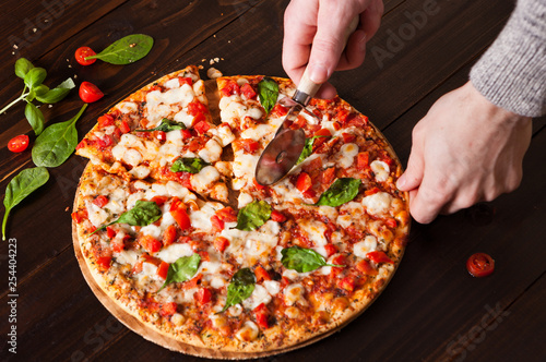 Fotografie, Obraz  Fresh margherita pizza with two Caucasian human hands