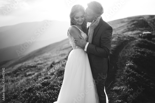 Foto Beautiful wedding couple, bride and groom, in love on the background of mountain