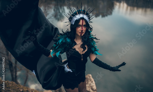 Photographie A woman in the image of a fairy and a sorceress standing over a lake in a black dress and a crown