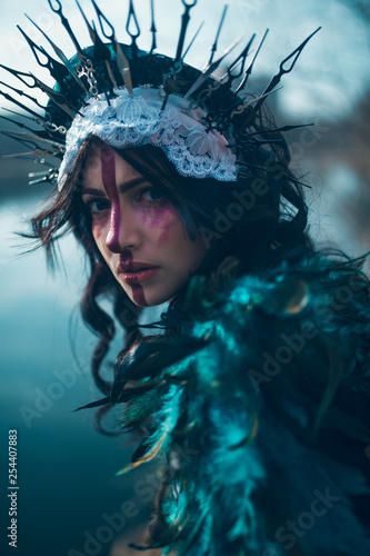 Portrait of young woman in the image of a fairy and a sorceress standing over a lake Tableau sur Toile