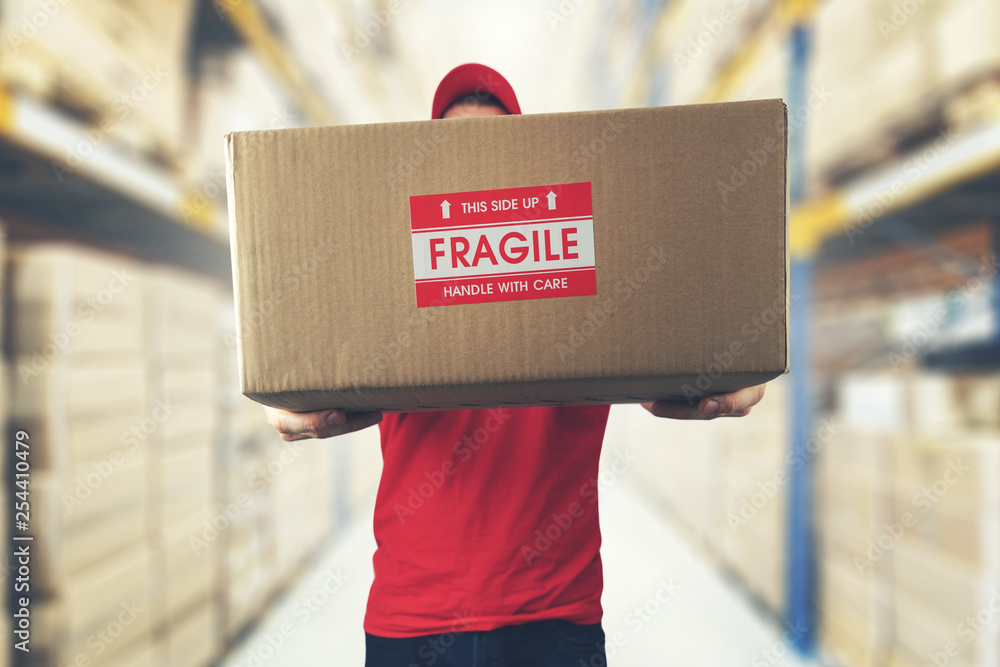 Fototapeta logistics warehouse worker holding package with fragile items