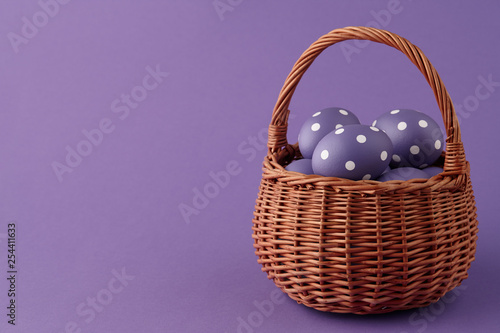 Fototapeta Wicker basket with purple painted Easter eggs with dots