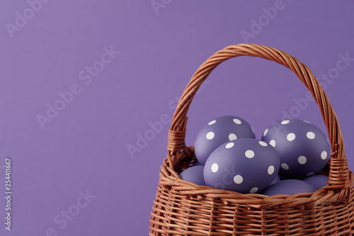 Fotografija Wicker basket with purple painted Easter eggs with dots