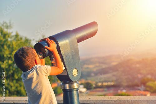 Foto  Little boy looking into tourist telescope eyepiece