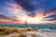 Leinwandbild Motiv Sonnenuntzergang über der Ostsee mit Segelboot