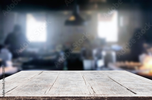 Wooden table on abstract blurred kitchen with Chef cooking in restaurant background and space for decoration display or montage your products.