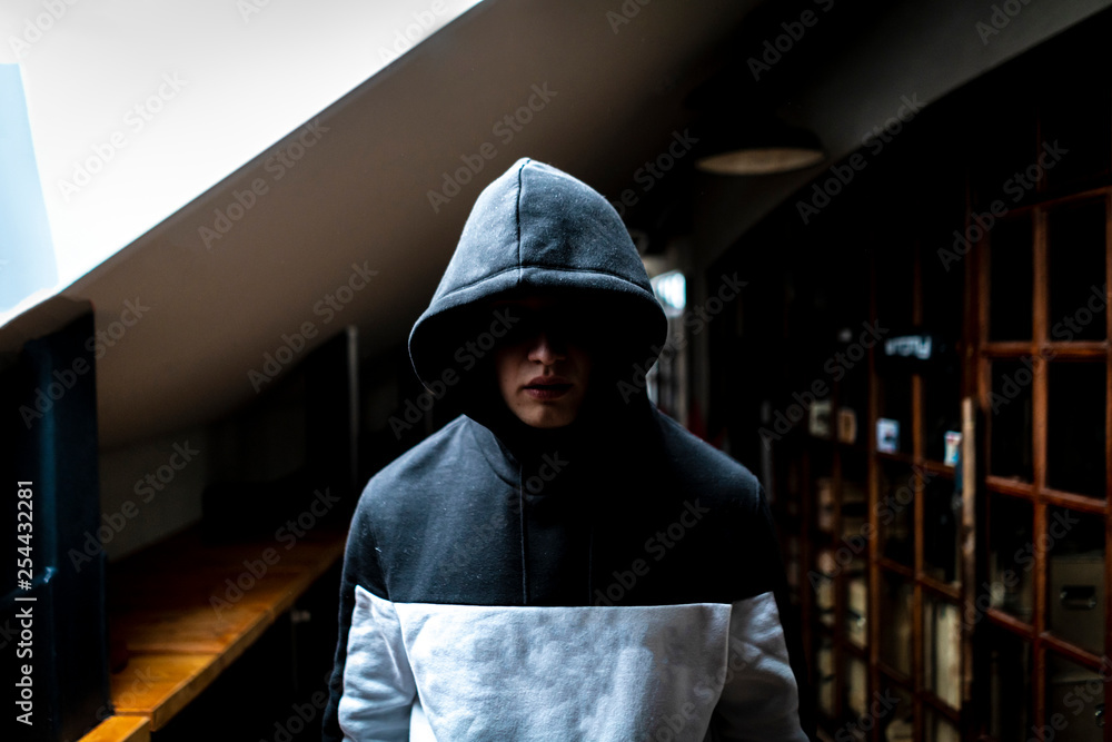 Fotografía  anonymous man in the dark hood standing in the mysterious pose f