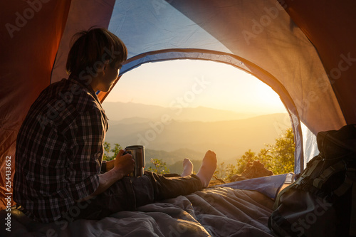 Montage in der Fensternische Schokobraun A young man sitting in the tent with holding coffee cup, looking at the mountain landscape in winter.Light effects