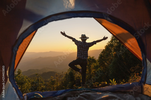 Papiers peints Dragons Happy man stay near tent around mountains under sunset light sky enjoying the leisure and freedom.