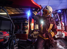Fireman Wearing A Protective Uniform With Flashlight Included Working In A Fire Station Garage