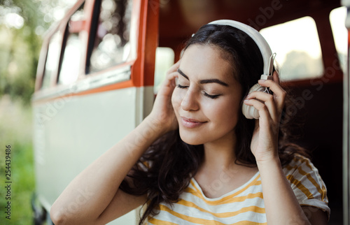 A young girl with headphones on a roadtrip through countryside, listening to music. - 254439486