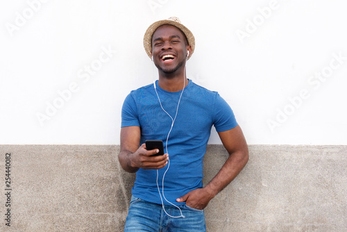 happy african american man listening to music with cellphone and earphones - 254440082