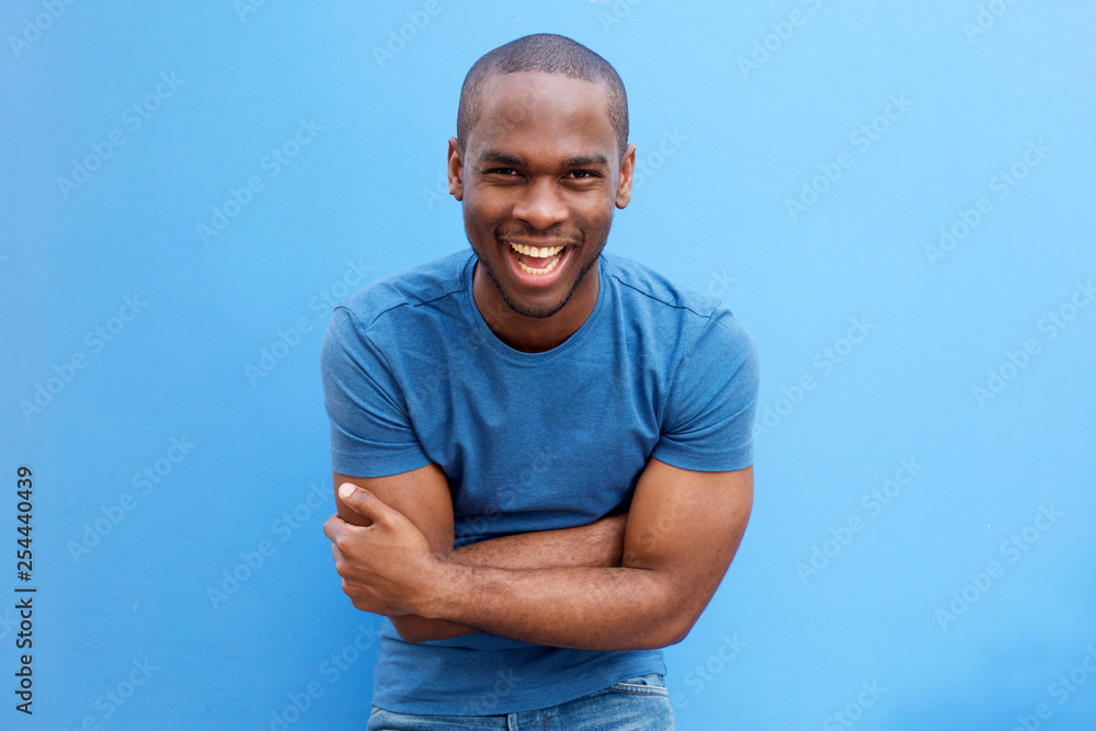 Fototapety, obrazy: handsome young african american man laughing with arms crossed