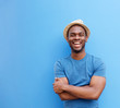 canvas print picture - handsome young black guy with hat smiling against blue background