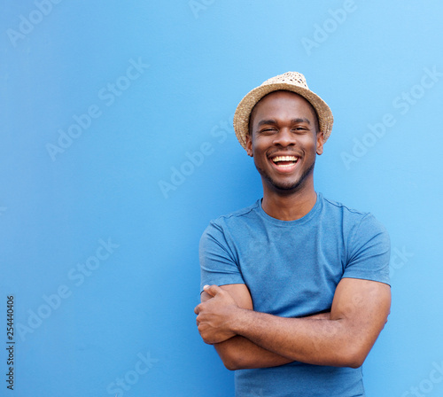 handsome young black guy with hat smiling against blue background Wallpaper Mural
